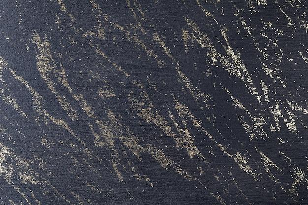 Noir avec des paillettes dorées. surface sombre parsemée de cristaux d'or