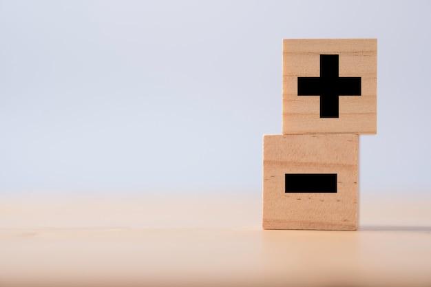 Noir de signe plus et moins sur cube en bois.