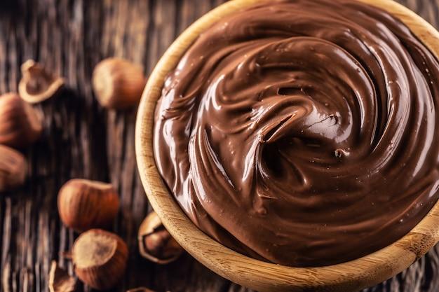 Noisette au chocolat à tartiner dans un bol en bois - gros plan.