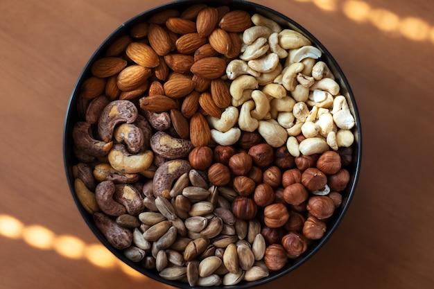 Noisettes, amandes, noix de cajou crues, noix de cajou frites et pistaches en assiette sur table en bois.