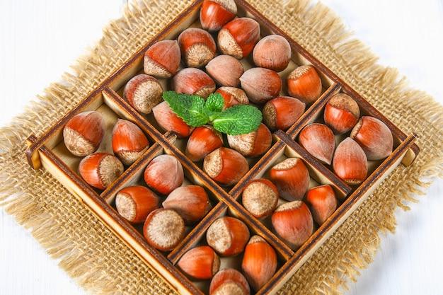Noisettes aux noix dans une boîte en bois carrée avec des diviseurs sur une table en bois blanche.