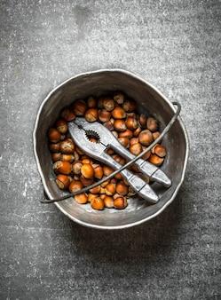 Noisettes avec casse-noisette dans l'ancien pot. sur la table en pierre.