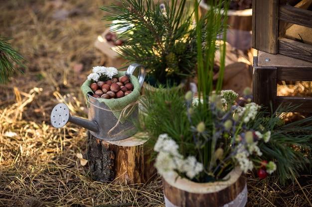 Les noisettes dans l'arrosoir près des décorations en bois et des fleurs des champs. tendance écologique pour un mariage rustique