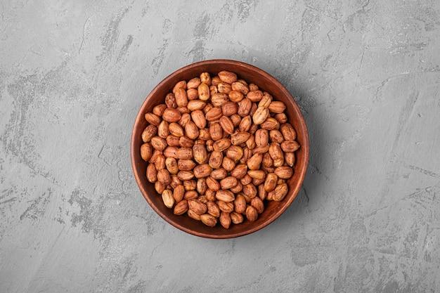 Noisettes dans un bol en bois sur fond de béton vue de dessus des aliments végétaliens sains naturels