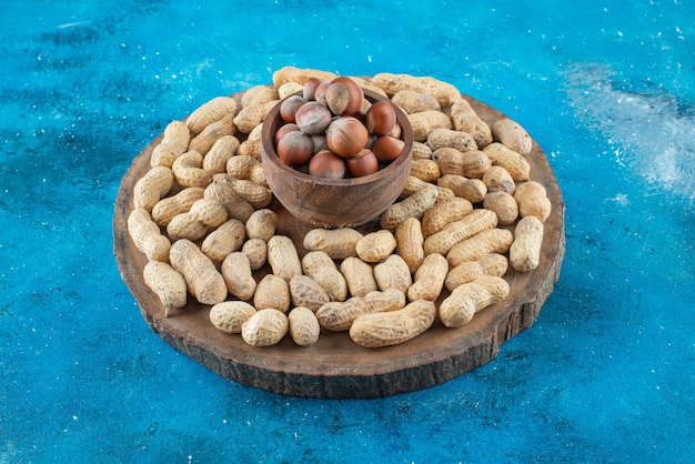 Noisettes dans un bol à bord avec des cacahuètes , sur la table bleue.