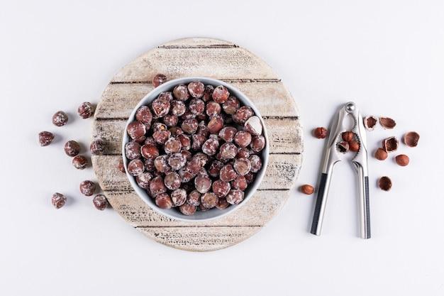 Noisettes décortiquées dans un bol blanc avec vue de dessus de casse-noisette sur une planche à découper en bois