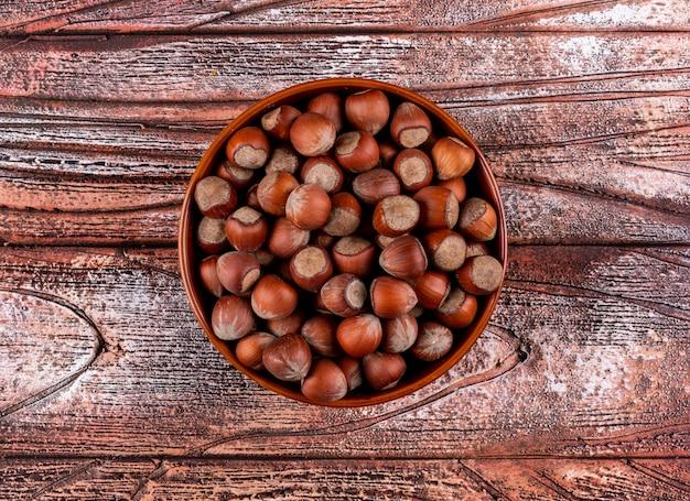 Noisettes décortiquées dans un bol brun sur une table en bois. mise à plat.