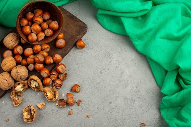 Noisettes et noix décortiquées et entières à l'intérieur du pot brun sur un tissu vert et clair