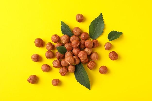 Noisettes savoureuses et feuilles sur jaune