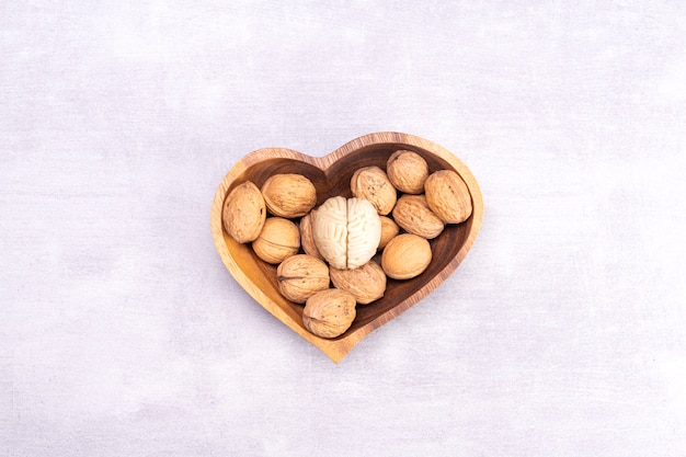 Les noix aiment les aliments sains pour le cerveau. la forme du cerveau humain est entourée de cerneaux de noix en forme de cœur