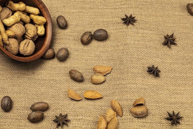 Noix amandes arachides dans un bol en bois sur fond de bois.