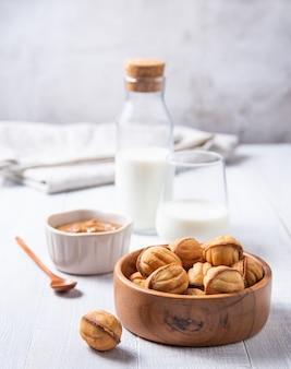 Noix au four au caramel dans un bol en bois et verre de lait sur une table blanche. vue de face