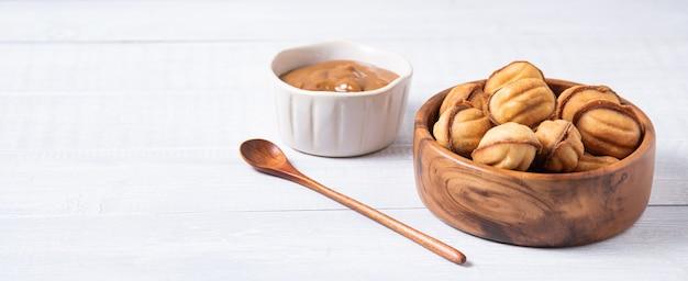 Noix au four avec du lait bouilli dans un bol en bois et caramel sur une table blanche. vue de face et espace de copie. image horizontale
