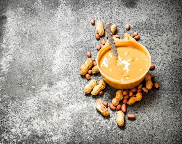 Noix et beurre d'arachide dans un bol sur table rustique.
