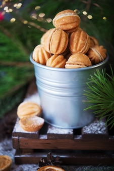 Noix de biscuits de bonbons de noël avec du lait concentré sur la table de fête, décorations de noël, mise au point sélective
