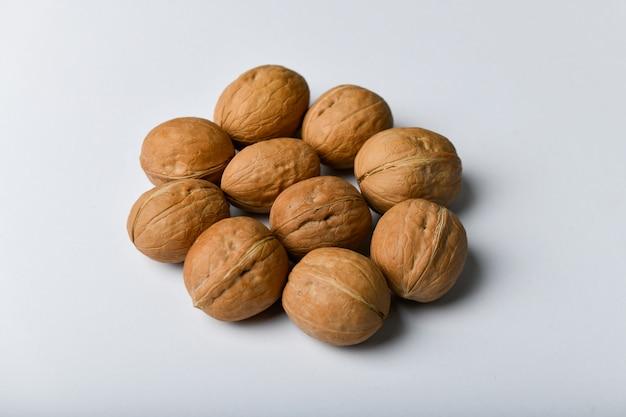 Noix sur un blanc. vue rapprochée de noix. les noix sont 4 eau, 15 protéines, 65 lipides et 14 glucides, dont 7 fibres alimentaires. dans une portion de référence de 100 grammes.