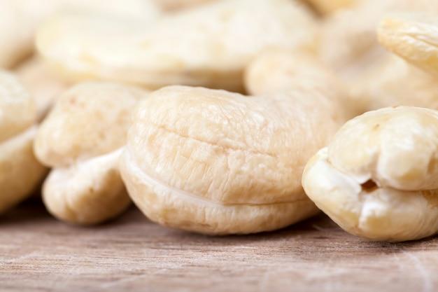 Noix de cajou crues délicieuses et saines, gros plan de noix de cajou pelées sur la table de la cuisine, noix de cajou croquantes