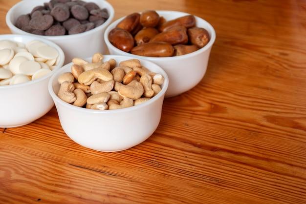 Noix de cajou, dattes, chocolat blanc et chocolat au lait dans des bols blancs.