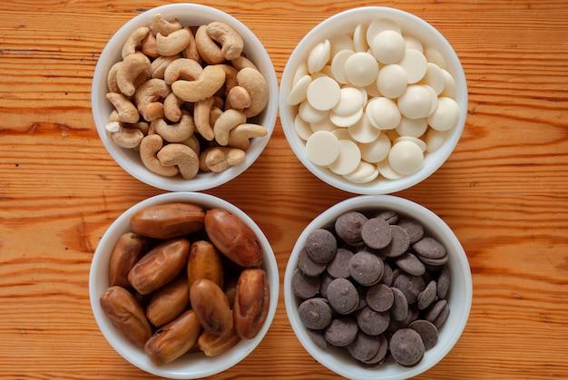 Noix de cajou, dattes, chocolat blanc et chocolat au lait dans des petits bols blancs.