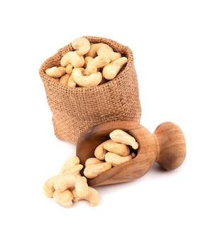 Noix de cajou en sac et cuillère en bois, isolé sur fond blanc. noix de cajou grillées.