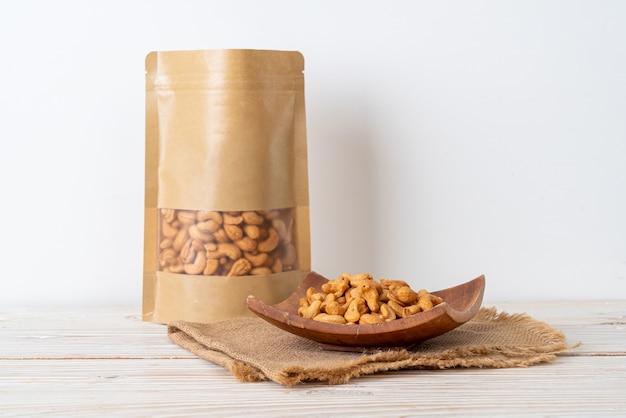 Noix de cajou en sac sur table en bois