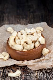 Noix de cajou sèches sur une vieille table en bois et dans un bol en bois, un tas de noix de cajou sur la table et dans une assiette en bois en mangeant