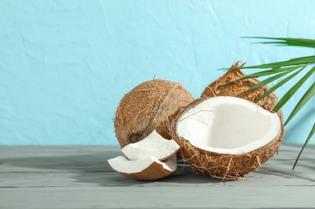 Noix de coco avec branche de palmier sur table en bois contre couleur
