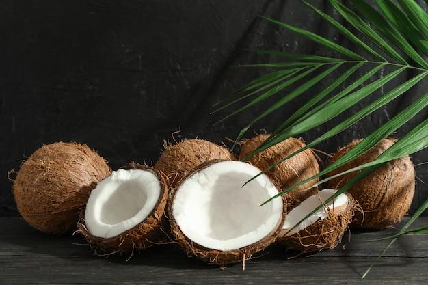 Noix de coco avec branche de palmier sur table en bois contre noir