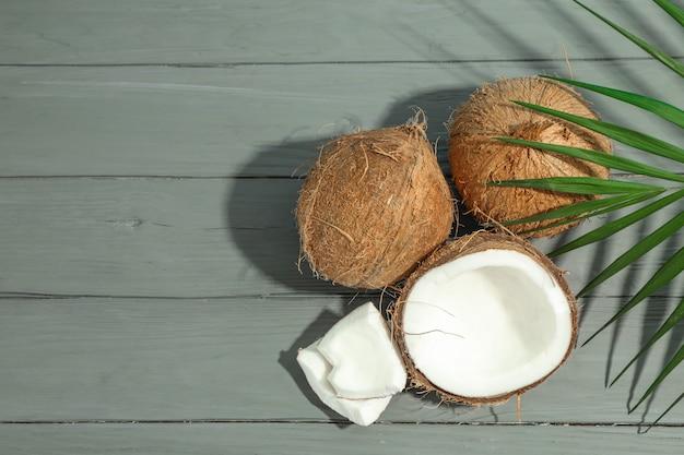 Noix de coco avec branche de palmier sur table en bois