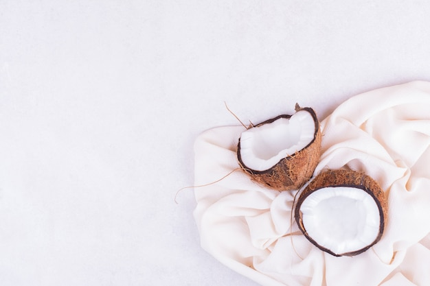Une noix de coco brune coupée en deux sur une serviette blanche