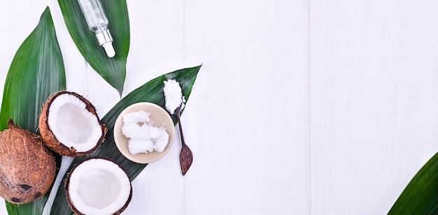 Noix de coco cassée et beurre. fruits exotiques sur fond blanc. espace libre pour le texte. copiez l'espace. mise à plat. bannière.