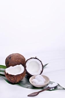 Noix de coco cassée et beurre. fruits exotiques sur fond blanc. espace libre pour le texte. copiez l'espace.