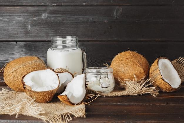 Noix de coco cassée et lait de coco sur fond en bois noir