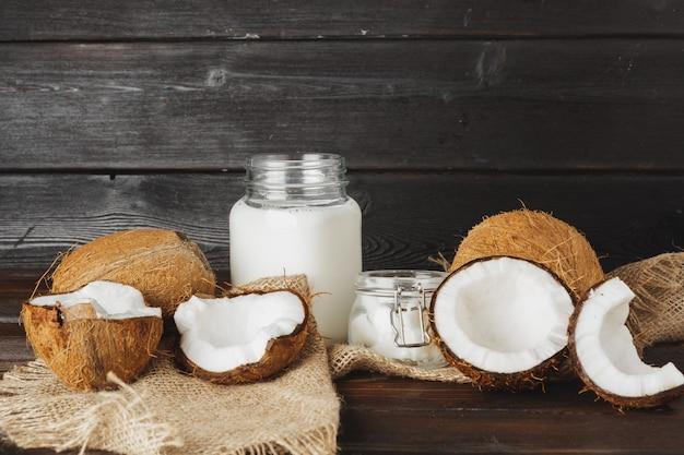 Noix de coco cassée et lait de coco sur fond de bois noir