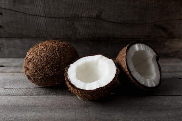 Noix de coco cassées sur fond de bois gris. pulpe de noix de coco blanche. photo de haute qualité