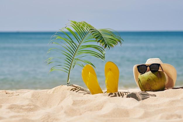 Noix de coco en chapeau de paille et lunettes de soleil sur la plage