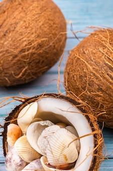 Noix de coco et coquillages sur un fond en bois bleu. thème marin.