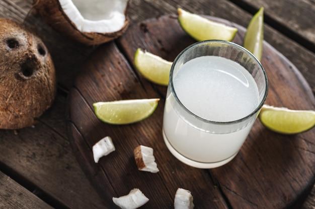 Noix de coco avec de l'eau de coco dans une tasse en verre sur une table en bois. concept de boissons saines