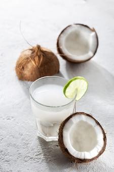 Noix de coco avec de l'eau de coco dans une tasse en verre