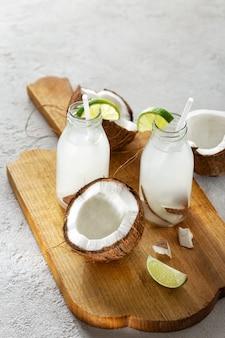 Noix de coco avec de l'eau de noix de coco en bouteilles sur table en bois. concept de boissons saines