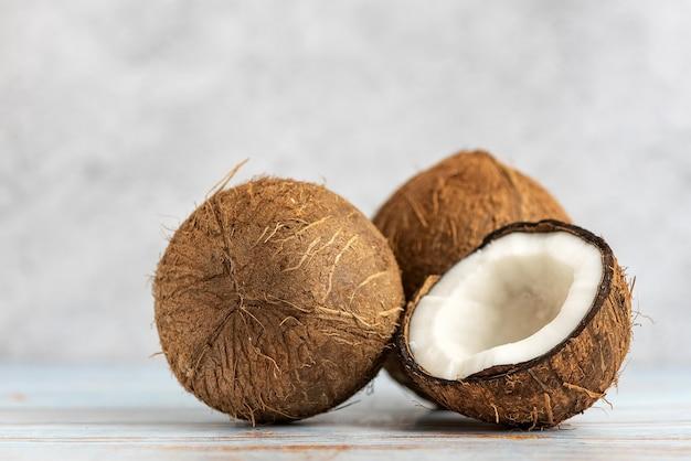 Noix de coco. entier et demi sur bois clair.