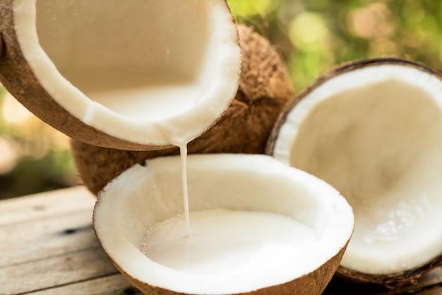 Noix de coco entière, moitié de noix de coco et lait de coco sur la surface de la nature.