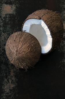 Noix de coco fendue en deux sur une surface sombre et minable.