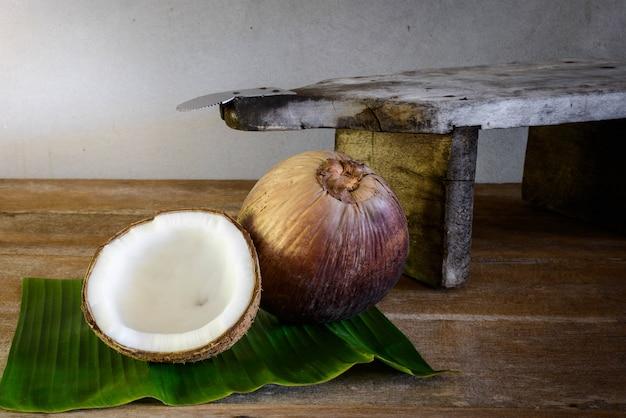 Noix de coco sur une feuille de bananier et une râpe à la noix de coco