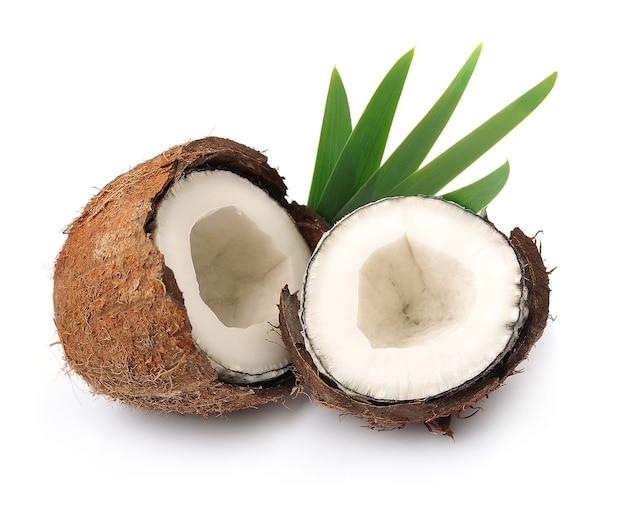 Noix de coco avec des feuilles sur un mur blanc
