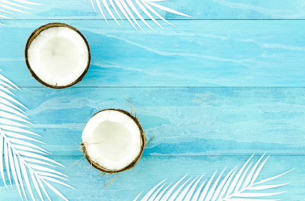 Noix de coco avec des feuilles de palmier sur une table en bois