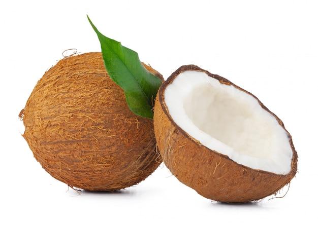 Noix de coco fissurée avec des feuilles isolé sur fond blanc