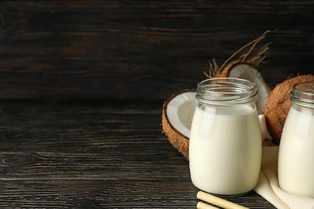 Noix de coco fraîche et lait de coco sur fond de bois
