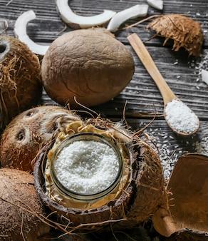 Noix de coco fraîches cassées sur un mur en bois