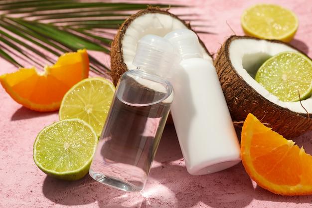 Noix de coco, fruits et cosmétiques sur rose, gros plan